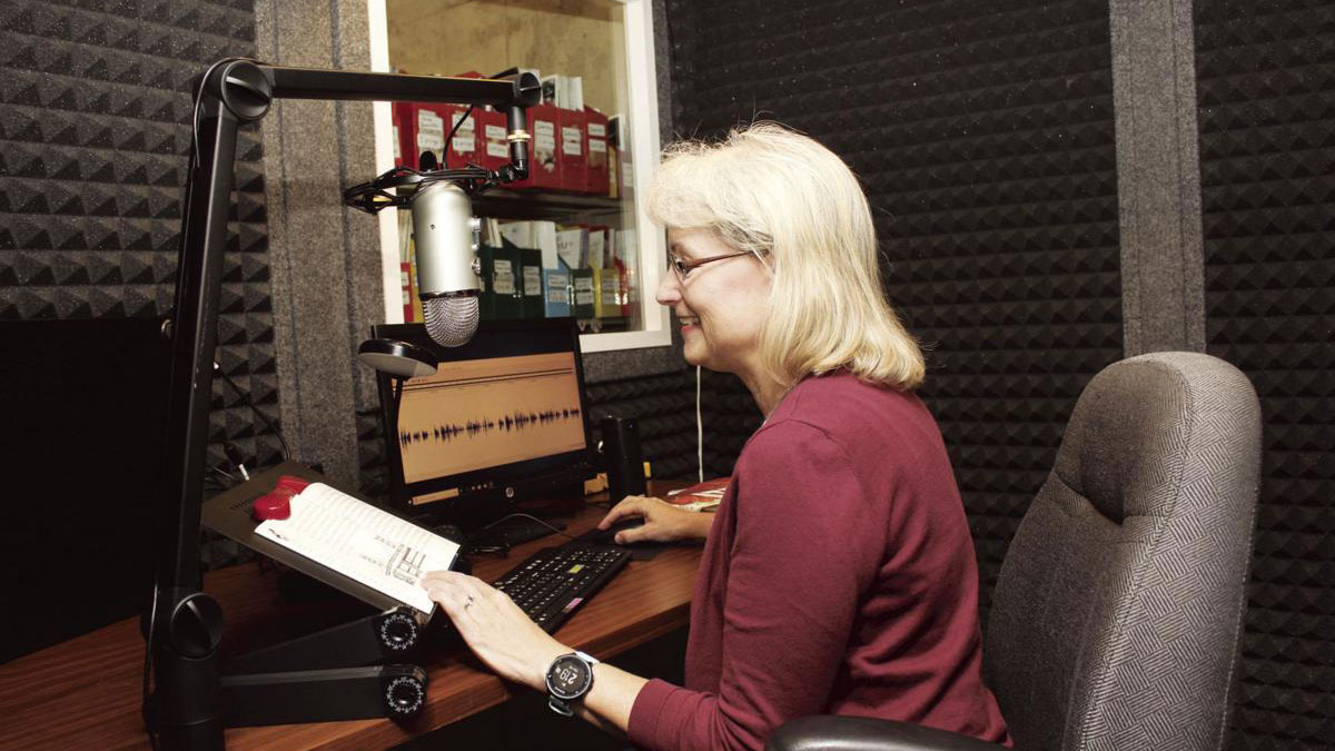 Volunteer Kathleen Bergeson using the new recording studio room in Vermillion Public Library