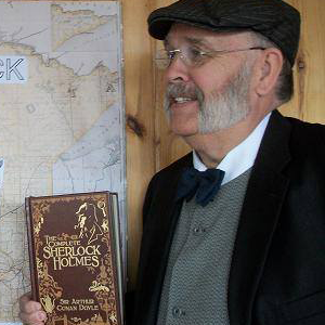 man wearing hat and holding sherlock holmes book